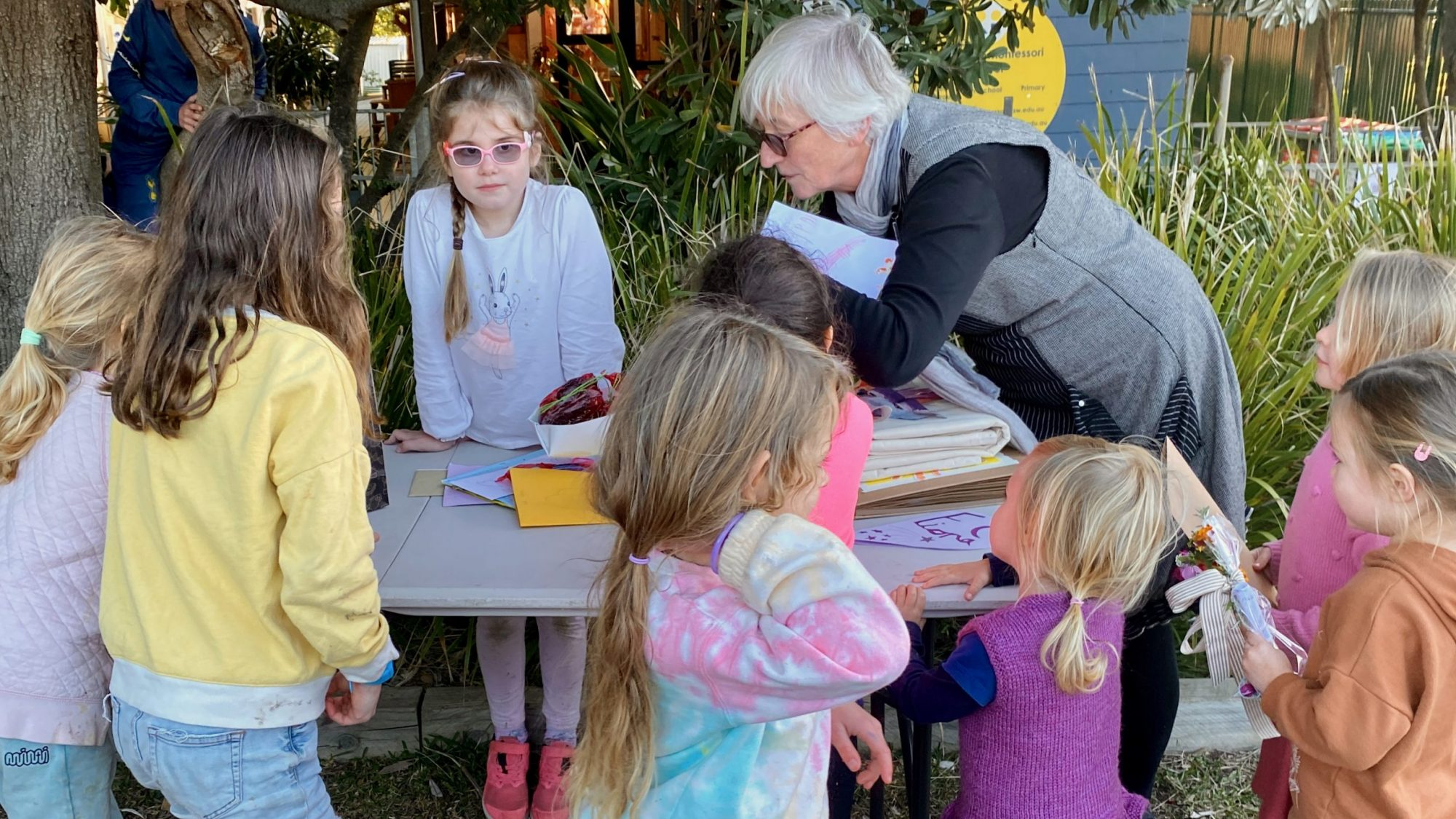 Barrenjoey Montessori principal Fiona Campbell looks at farewell gifts surrounded by students